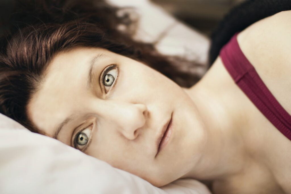 Young woman lies in bed, haunting eyes wide open following a night of insomnia, and ponders what today will bring - more of the same exhaustion, depression and sadness ?